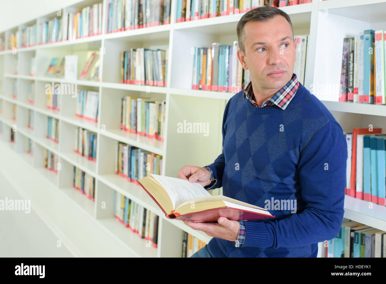 man holding a book - Stock Image