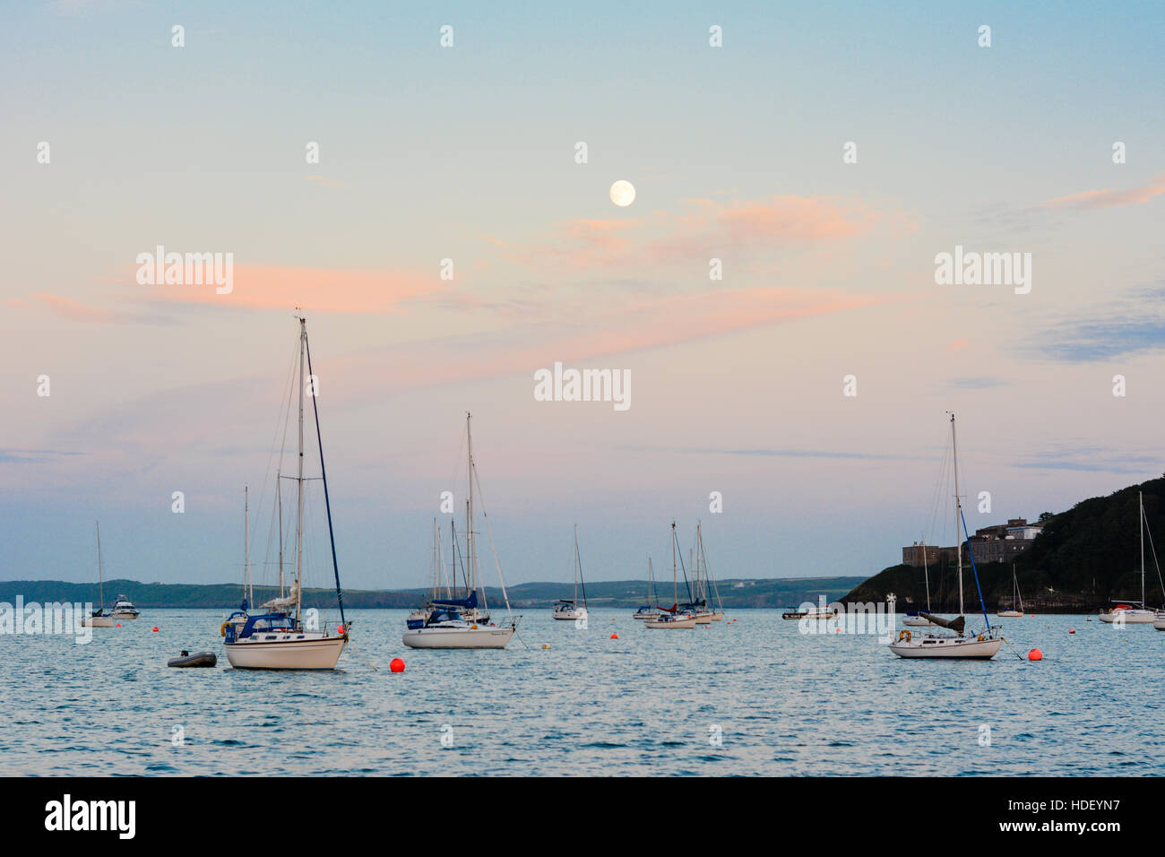 Full moon over yachts anchored on a calm turquoise sea with red cirrus clouds. - Stock Image