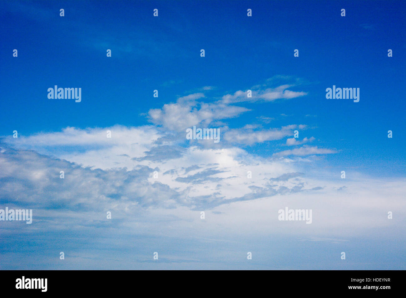 Patterned white clouds in a blue sky. - Stock Image