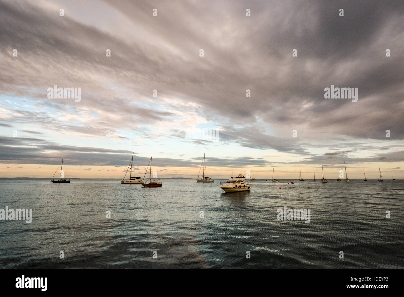 Yachts anchored at Dale on a calm summers evening at the start of a dramatic sunset. - Stock Image