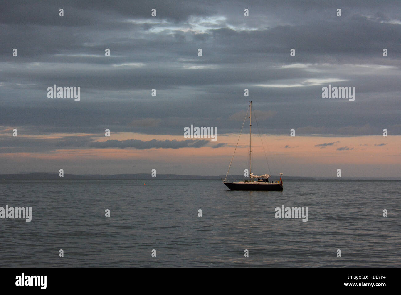 A yacht anchored on a calm summers evening with a tranquil sunset. - Stock Image