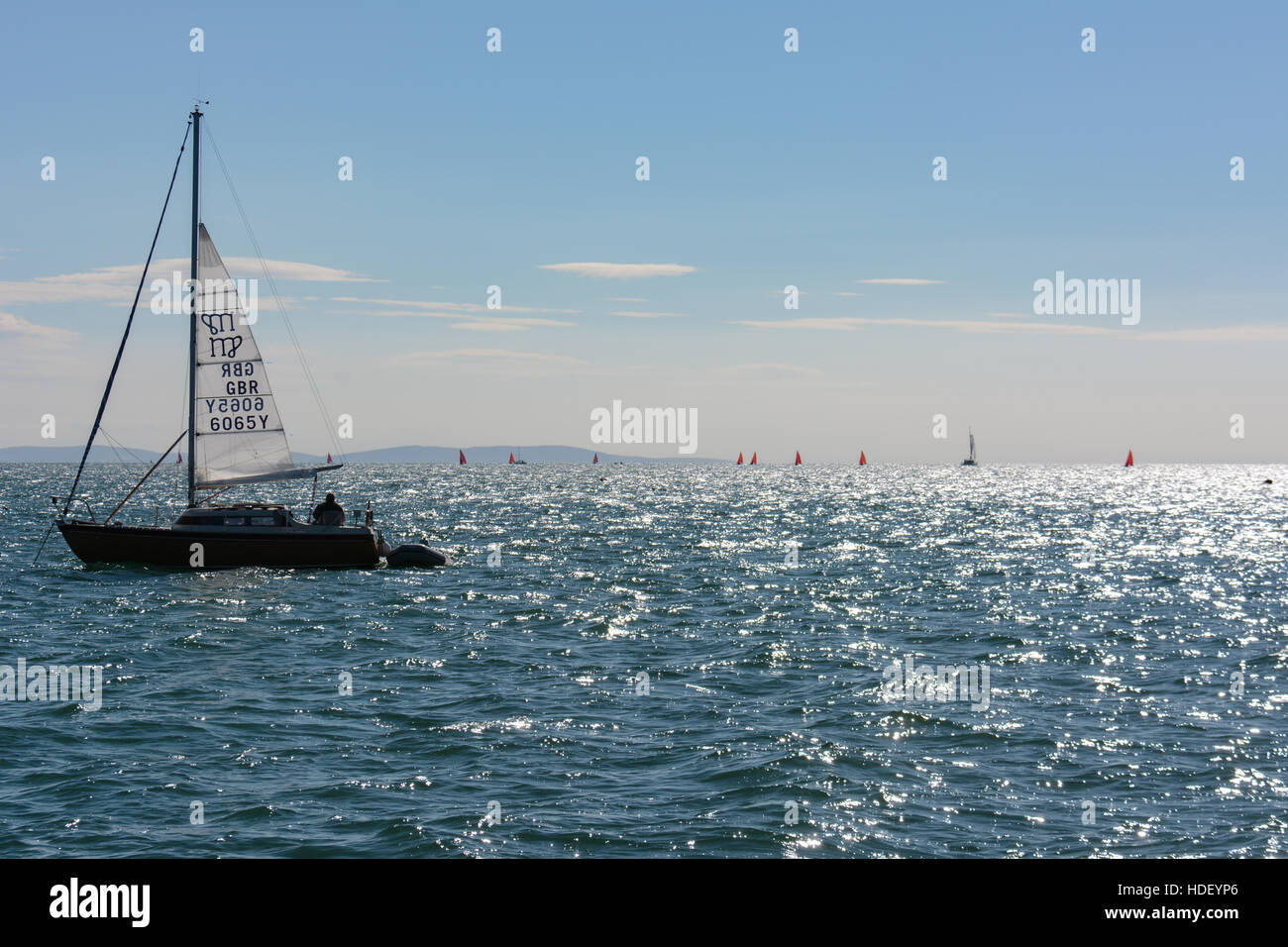 An anchored yacht with the mainsail partly raised as a steadying sail watches dinghy racing on a summers morning. - Stock Image