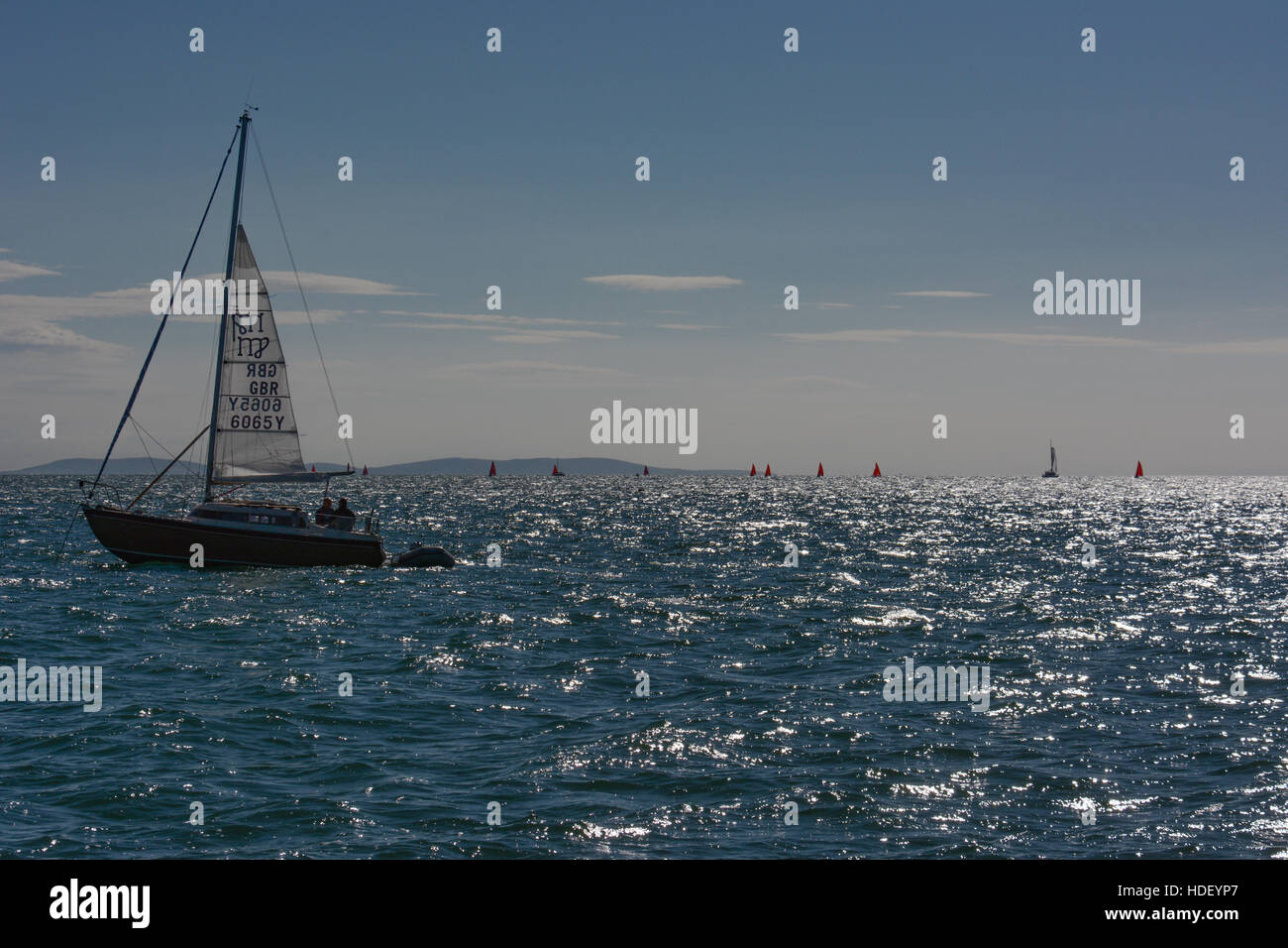 An anchored yacht with the mainsail partly raised as a steadying sail watches dinghy racing on a summers morning. Stock Photo