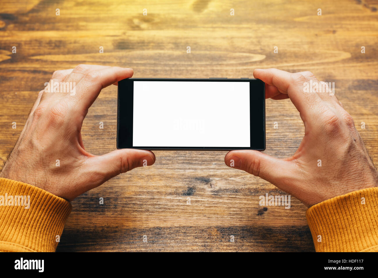 Man using smart phone in horizontal landscape orientation for streaming movies or browsing picture gallery, blank - Stock Image