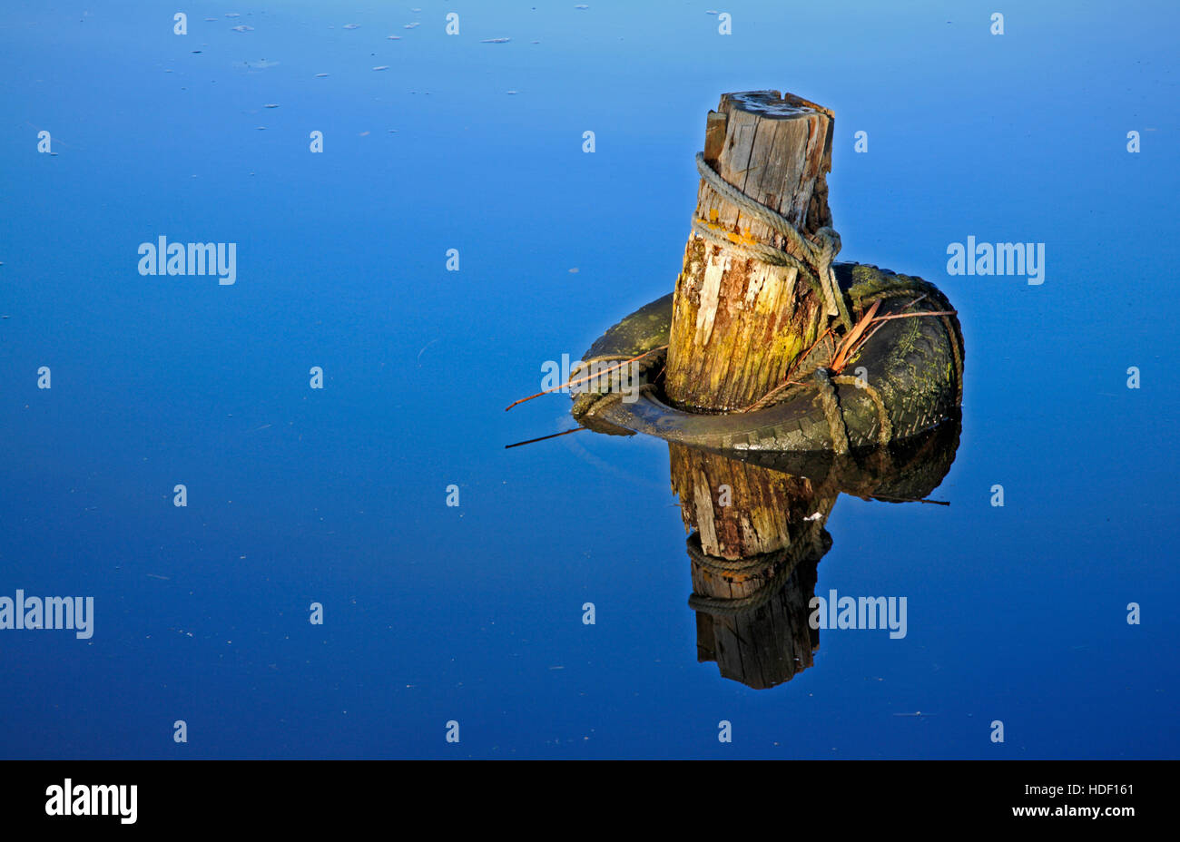 An old mooring post and tyre fender with reflection in the River Thurne on the Norfolk Broads. BHZ. - Stock Image