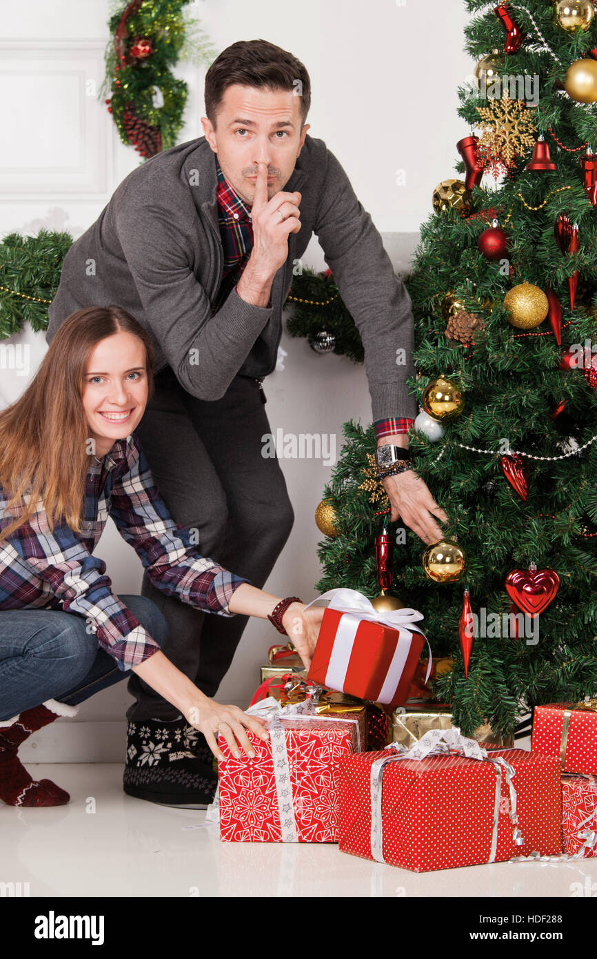 Happy parents with finger on lips put christmas gifts for children ...