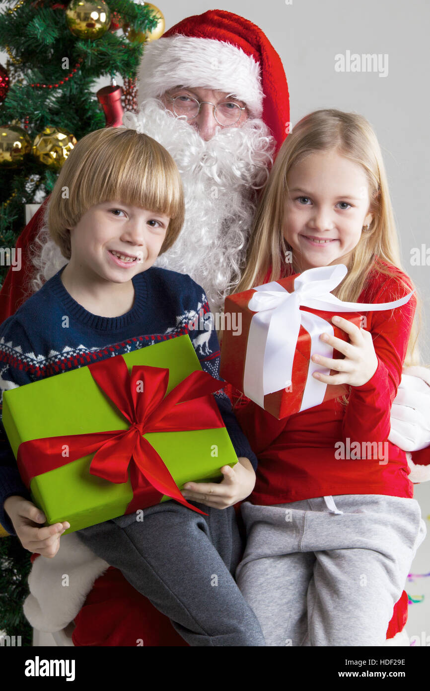Santa Claus and children with christmas gifts near christmas tree ...