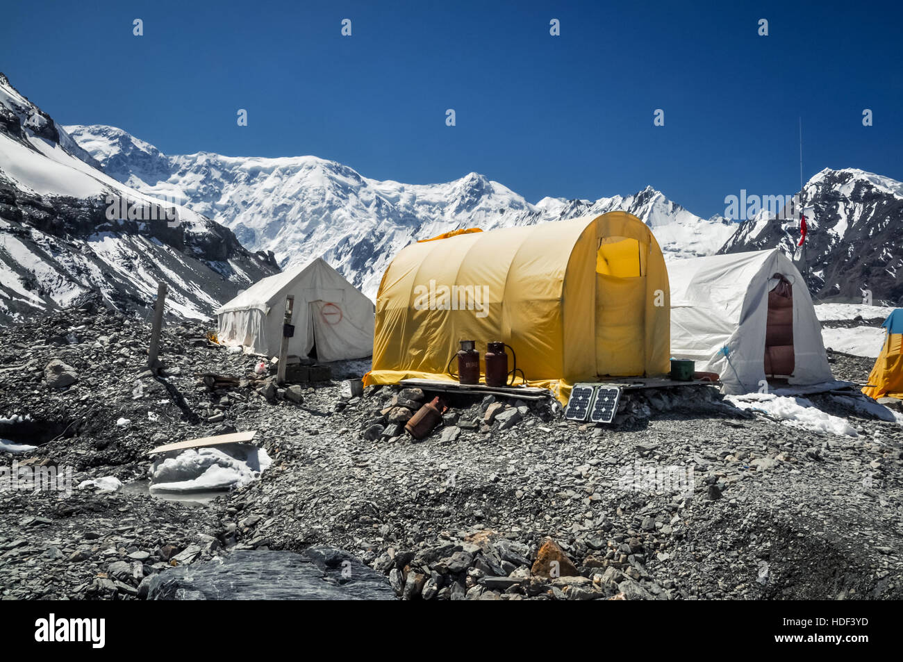 Tents of hikers on rocky ground surrounded by mountain range near South Inylcheck Glaciar in Kyrgystan. - Stock Image