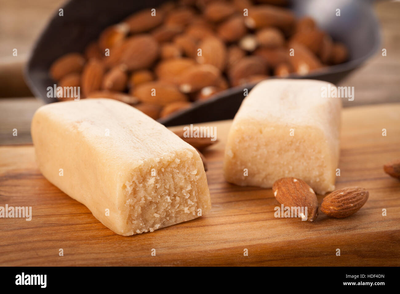 Marzipan bar and almonds on wooden chopping board Stock Photo