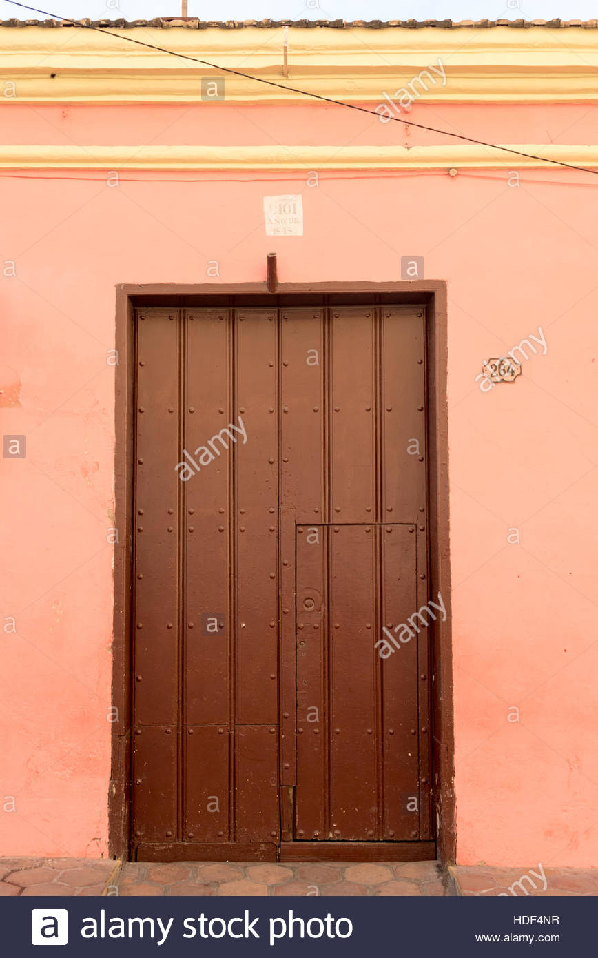 Colourful wooden door in old home. Spanish colonial architectural detail in urban houses of tropical Santiago de Stock Photo