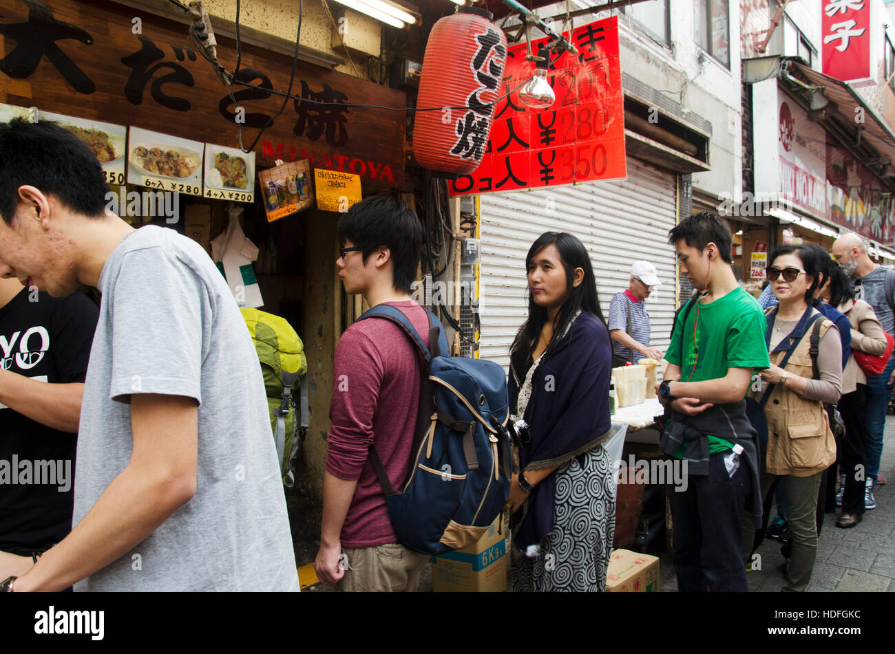 Japanese people and travelers foreigner standing queue buy takoyaki is a ball-shaped japanese snack at shop in Ameyoko Stock Photo