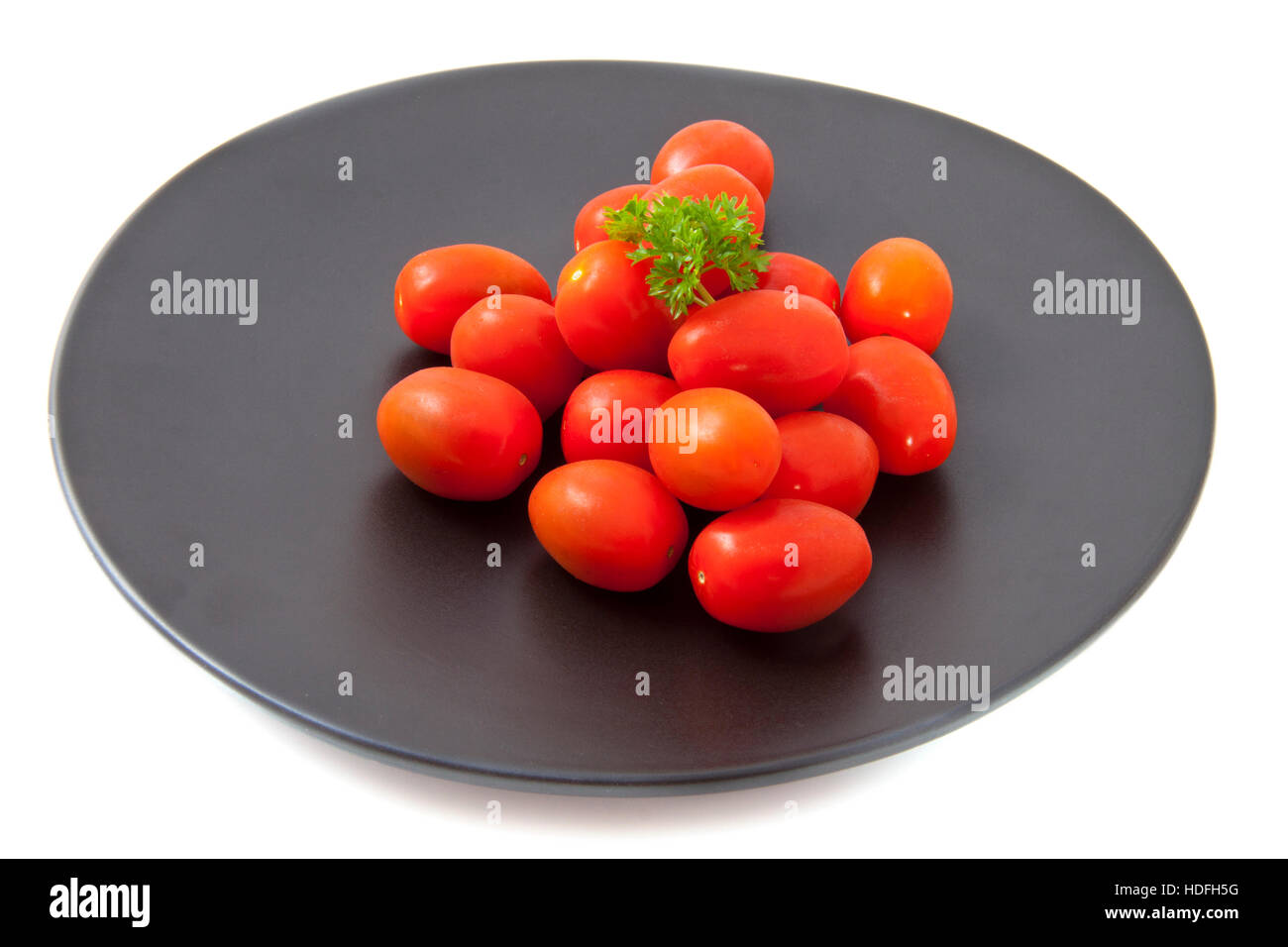 Little tomatoes on a black plate isolated over white - Stock Image