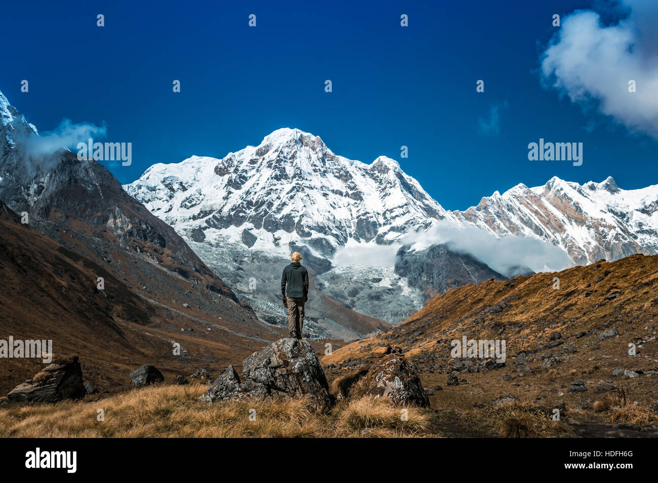 Young man stands alone in the mountains. - Stock Image