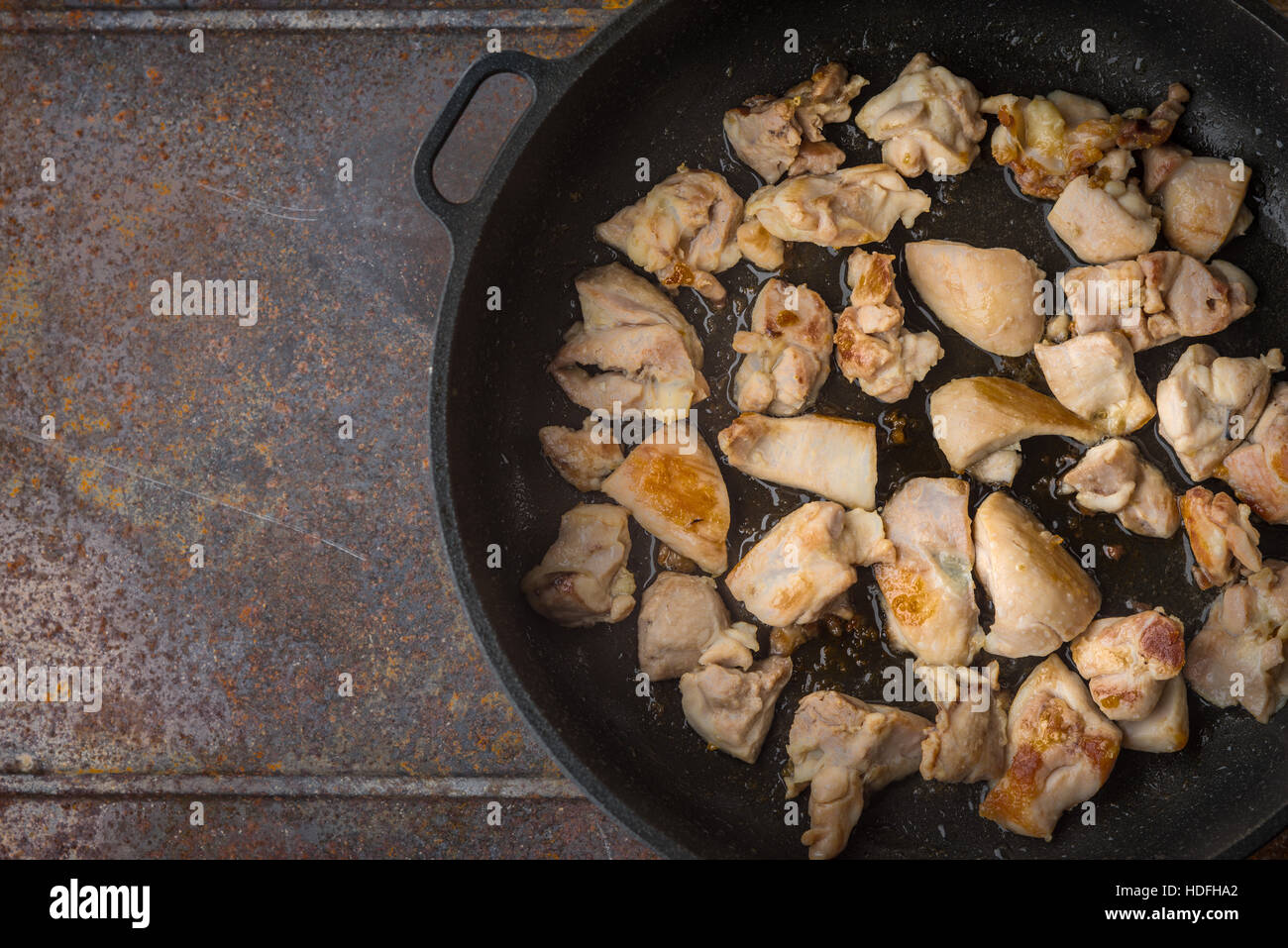 Fried chicken in the pan top view - Stock Image