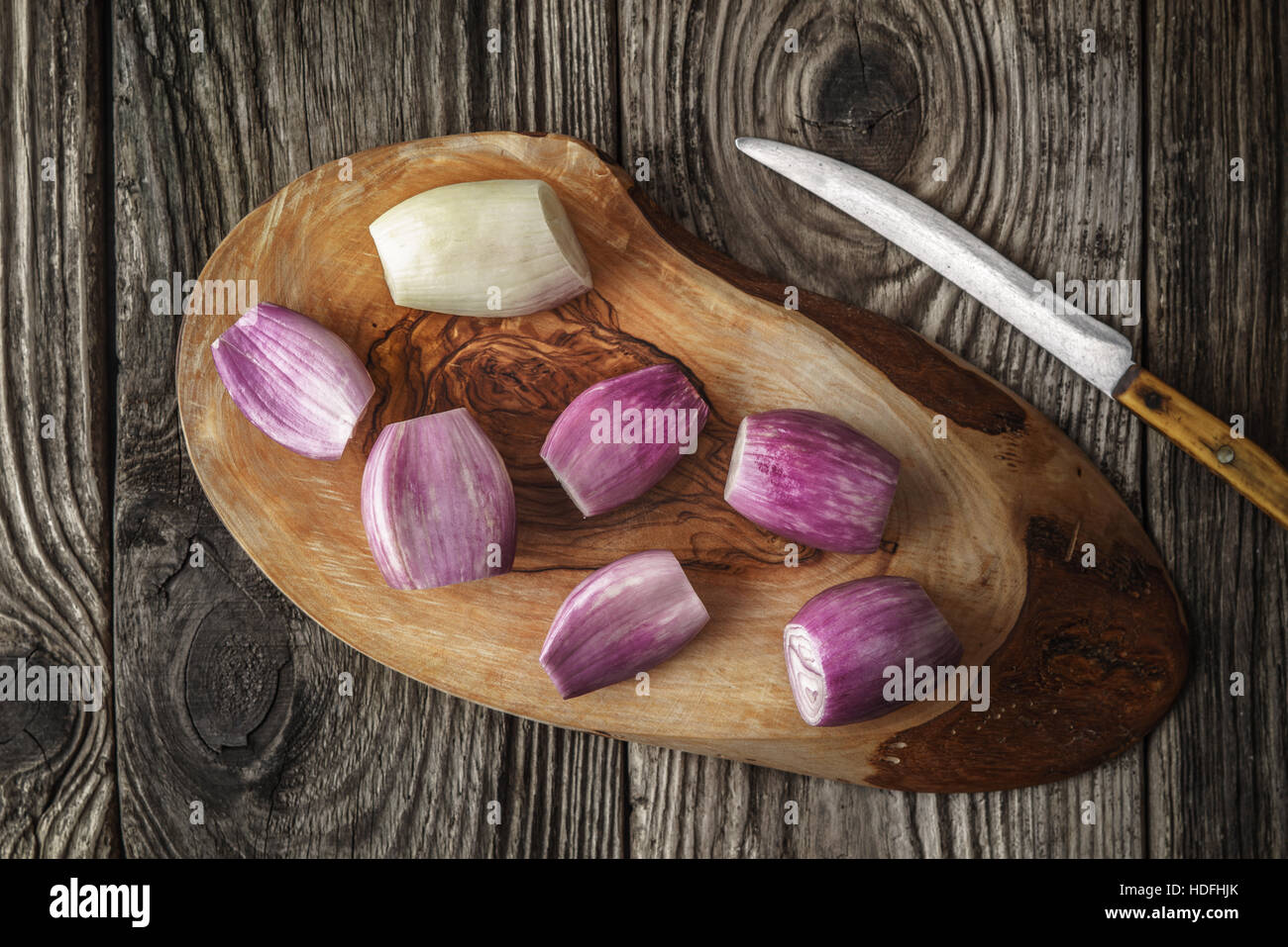 Shallot on the wooden board with knife top view - Stock Image