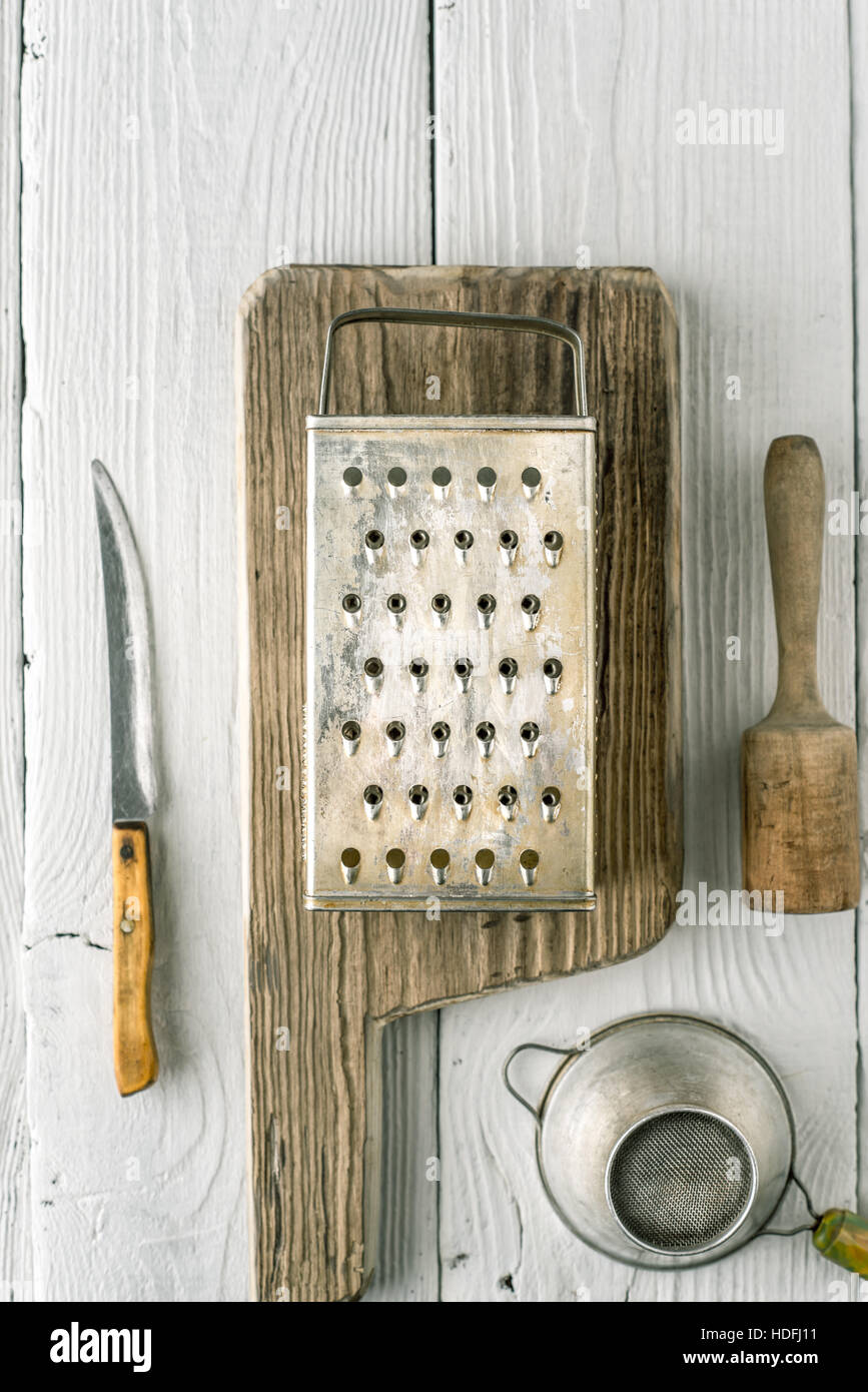 Grater, plunger , strainer and knife on the white wooden table vertical - Stock Image