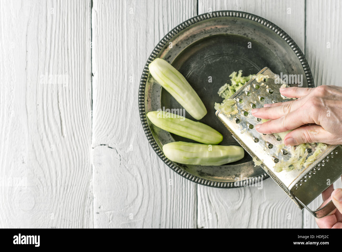 Grate cucumbers in the metal plate top view - Stock Image