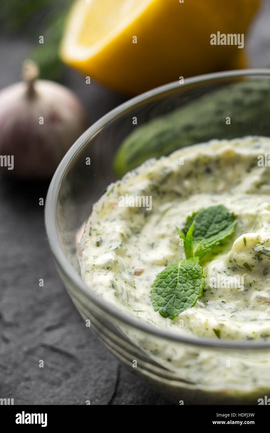 Tzatziki in the glass bowl on the black stone table vertical - Stock Image