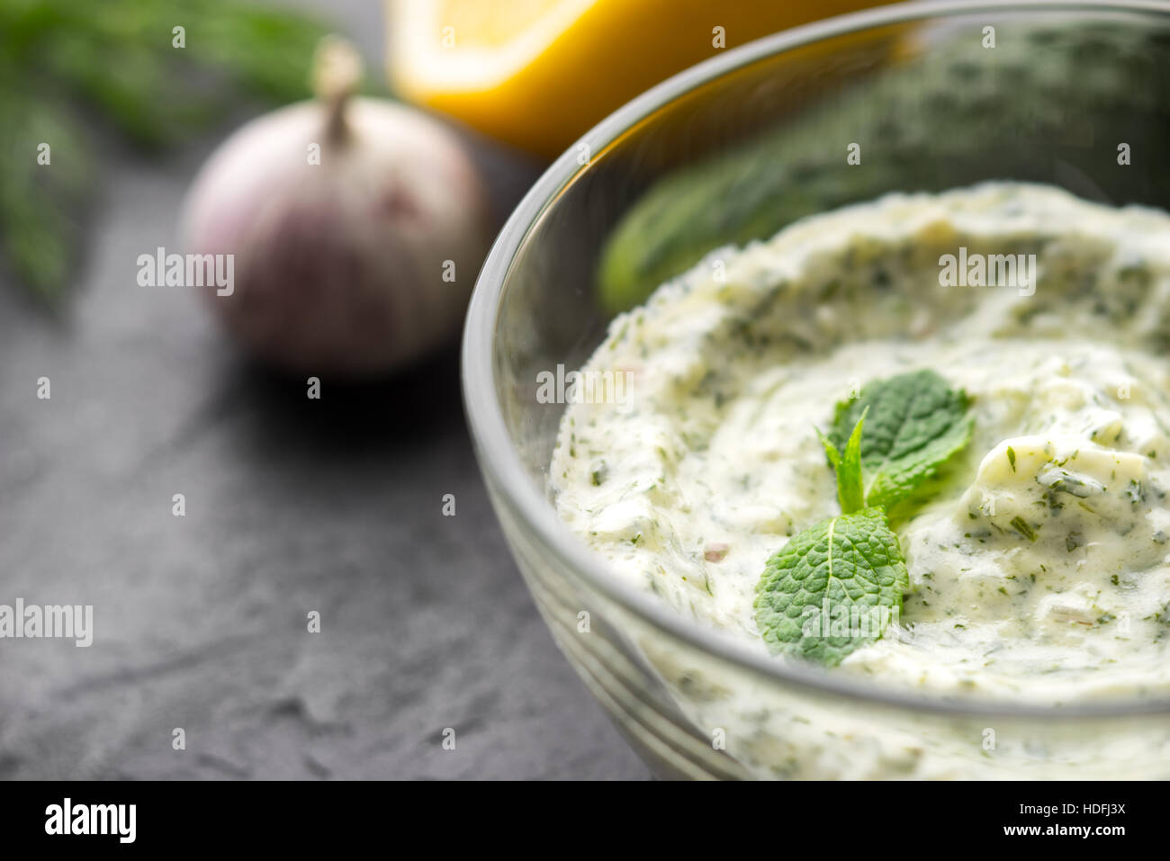 Tzatziki in the glass bowl on the black stone table horizontal - Stock Image