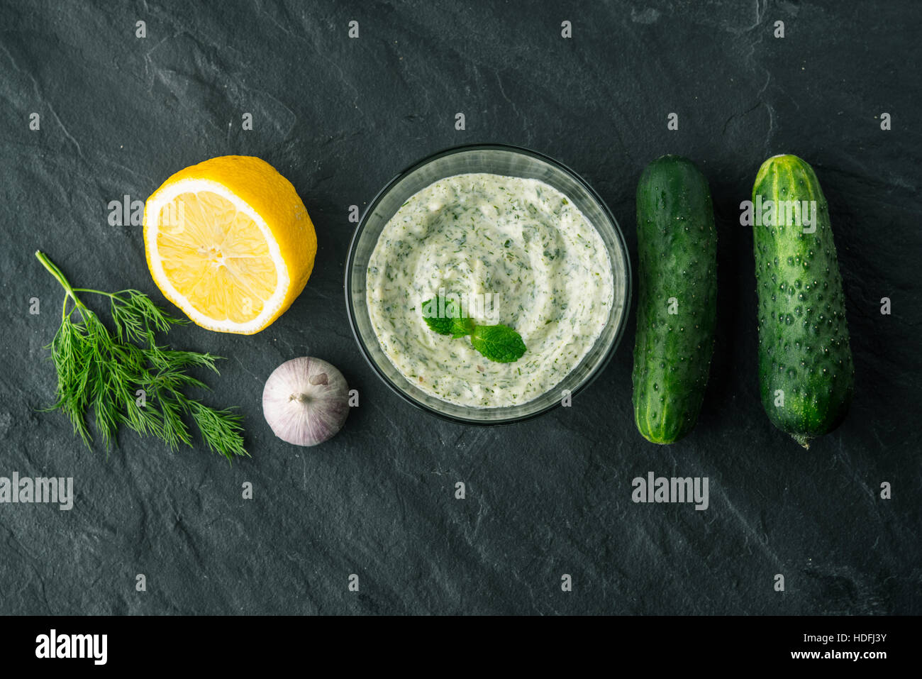 Tzatziki  on the dark stone table with ingredients top view - Stock Image
