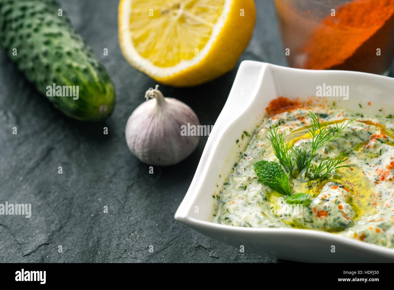 Tzatziki  on the stone table with cucumber , lemon and seasoning horizontal - Stock Image