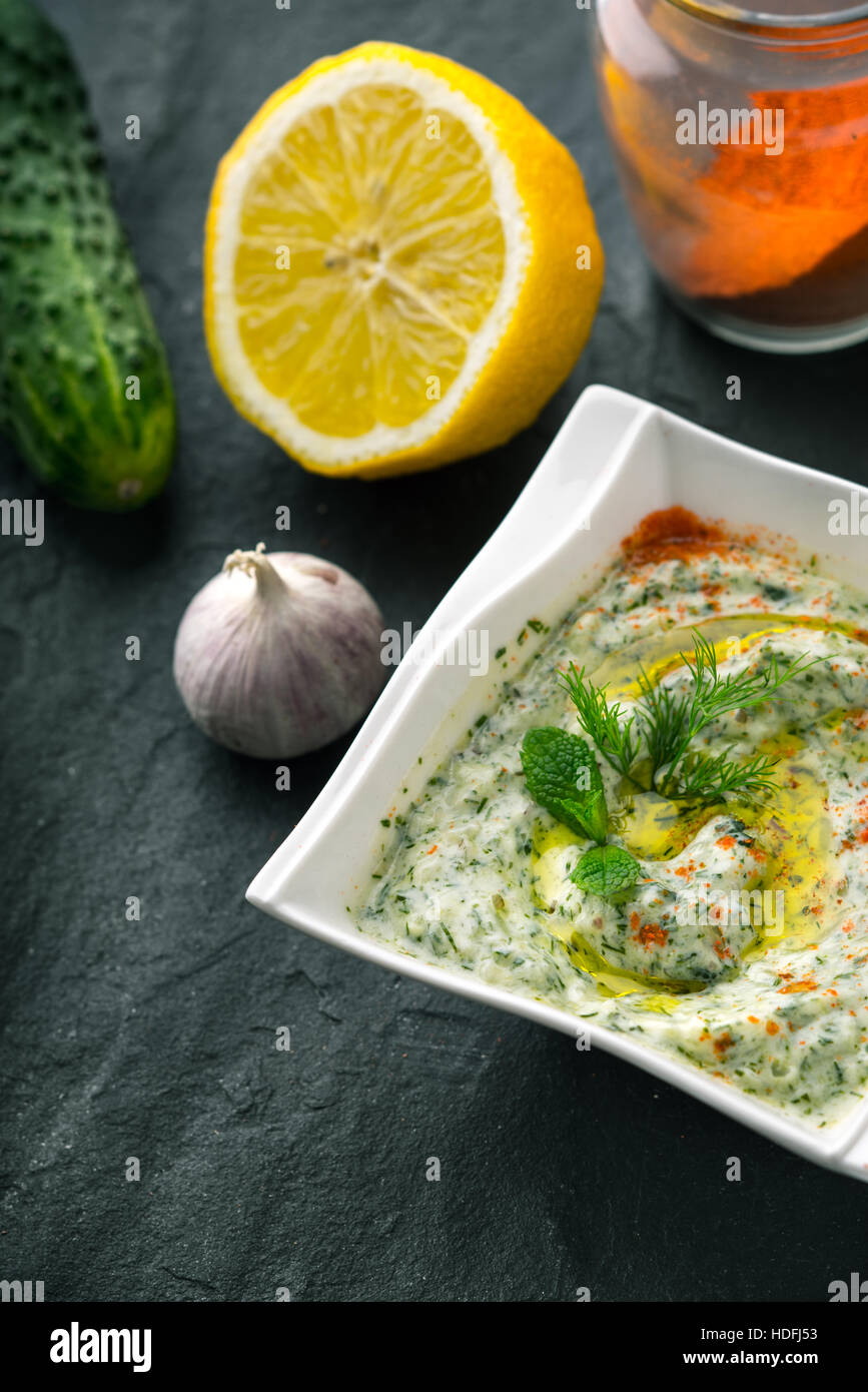 Tzatziki  on the stone table with cucumber , lemon and seasoning vertical - Stock Image