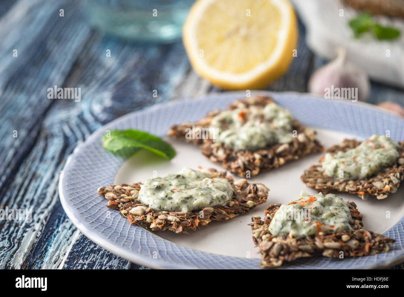 Crisp grain bread with tzatziki on the  blue ceramic plate horizontal - Stock Image