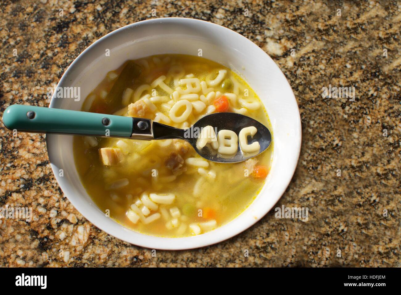 bowl of alphabet soup with the letters abc spelled out in noodles - Stock Image