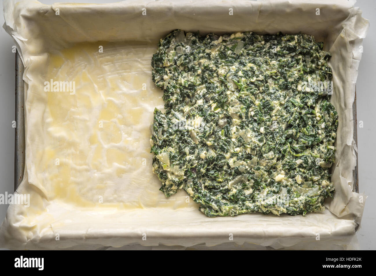 Placing the filling for spanakopita on the dough - Stock Image