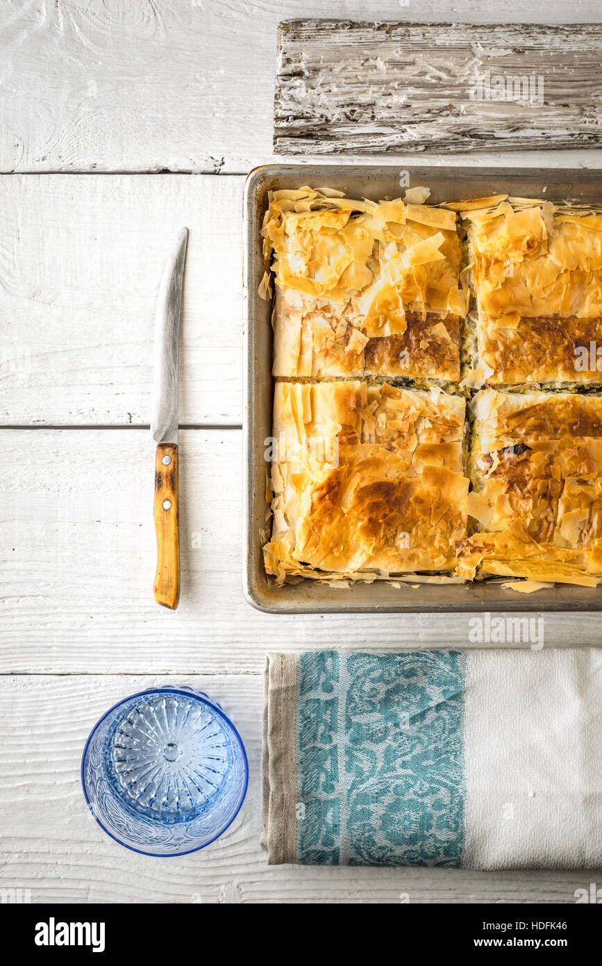 Greek pie spanakopita in the metal pan  with table ware vertical - Stock Image
