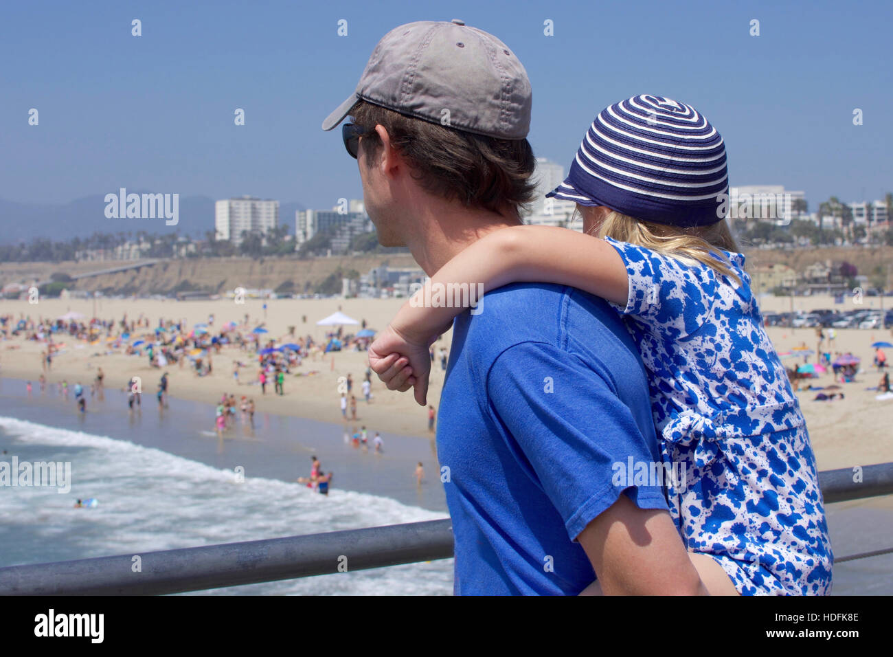 young girl riding piggy back with father on santa monica pier california Stock Photo