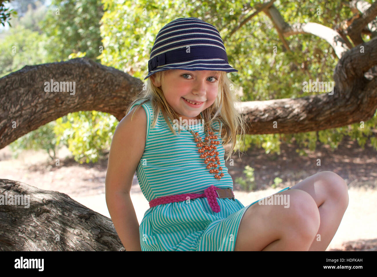 adorable school age girl sitting on tree in park in summertime - Stock Image