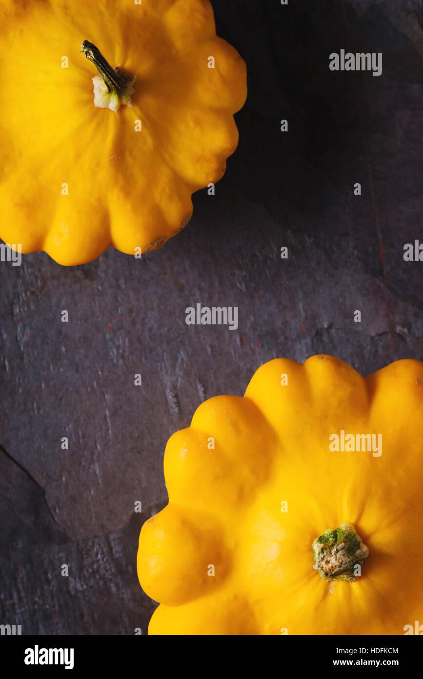 Yellow fresh squash patty pan on the dark stone background vertical - Stock Image