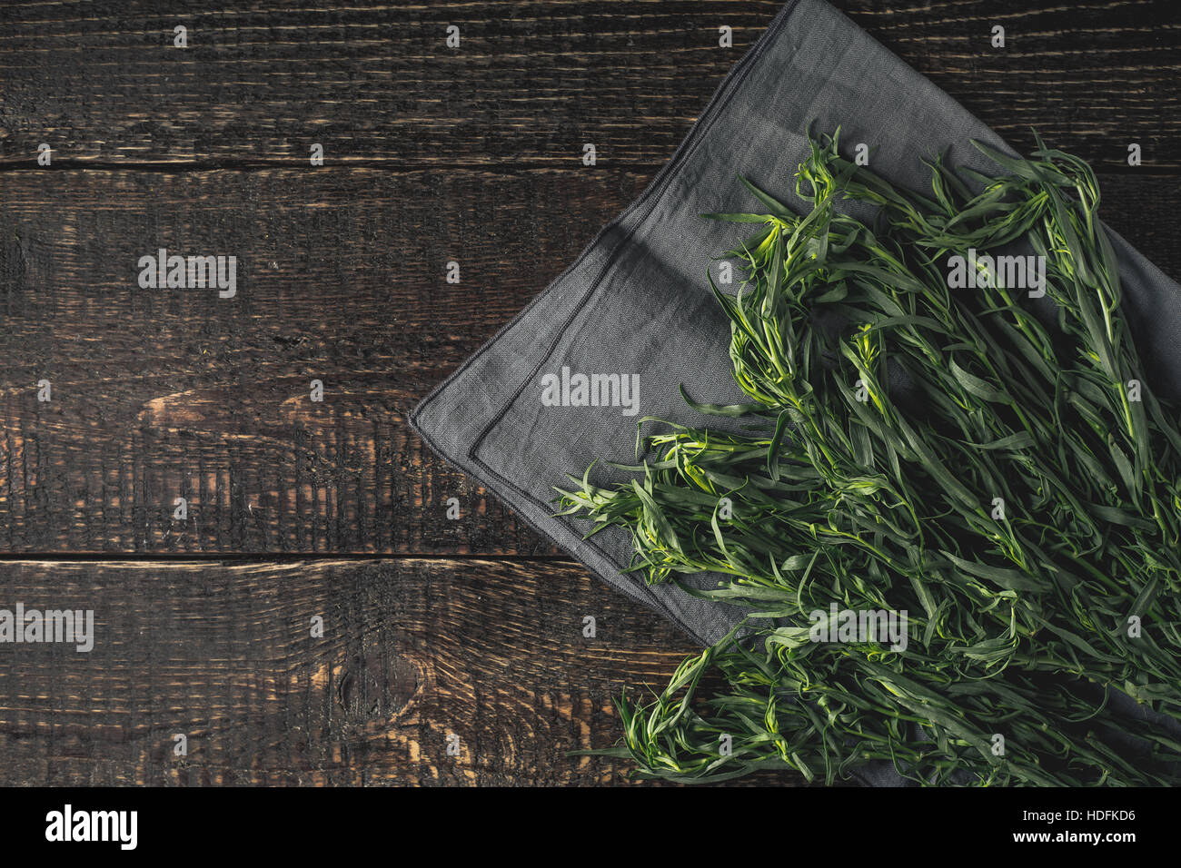 Tarragon on the grey napkin on the wooden table top view - Stock Image
