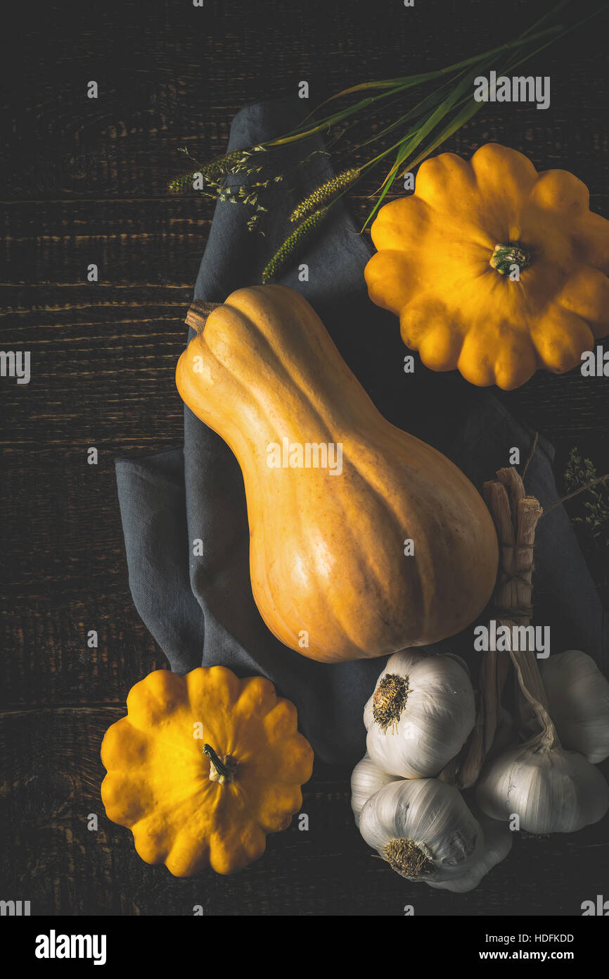 Pumpkin , patty pans and garlic on the old wooden table top view - Stock Image