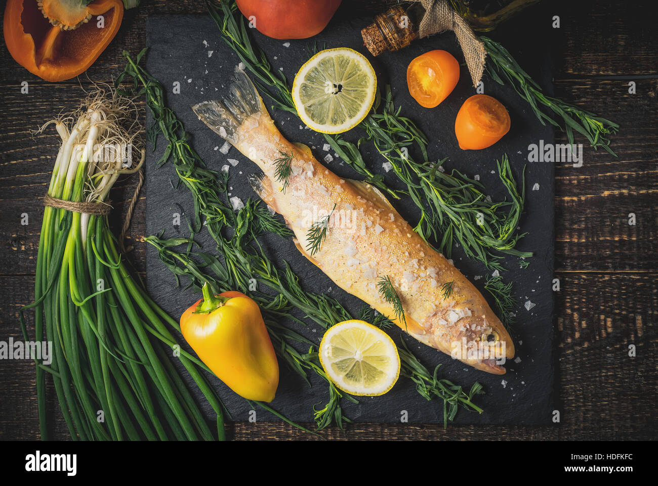 Raw golden trout with salt and vegetables on the wooden table top view - Stock Image