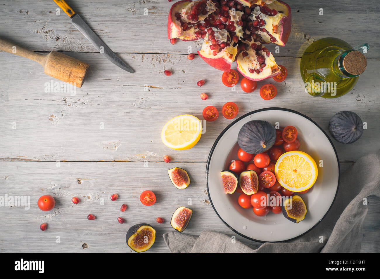 Pomegranate with figs and cherry tomatoes on the white wooden table top view - Stock Image