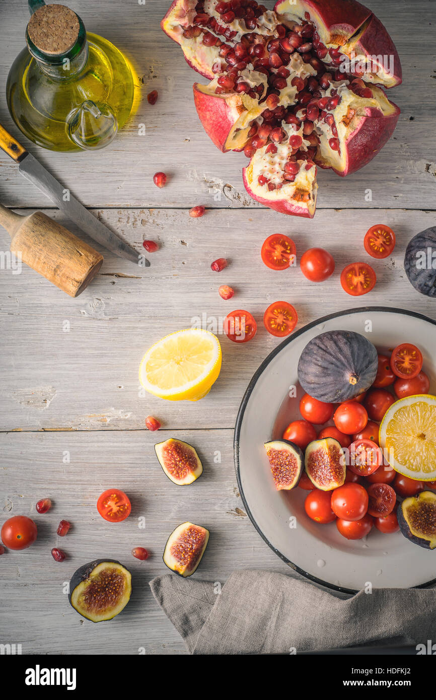 Pomegranate with figs and cherry tomatoes on the white wooden table vertical - Stock Image