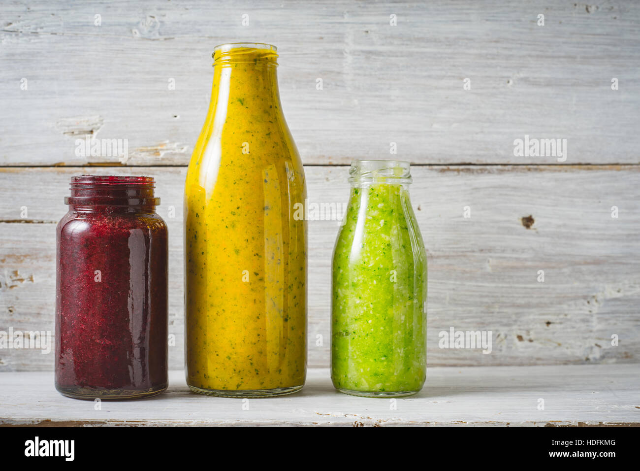 Green, yellow and red smoothie in the glass bottle on the white wooden background Stock Photo