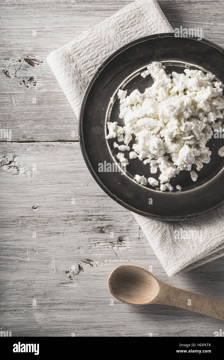 Fresh cottage cheese on the  metal plate on the white wooden table vertical Stock Photo