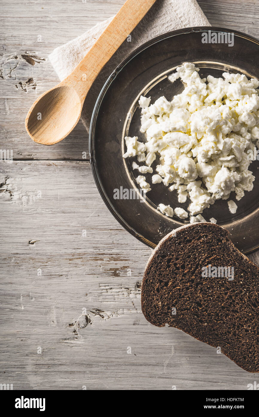 Fresh cottage cheese on the  metal plate  with bread on the white wooden table vertical - Stock Image