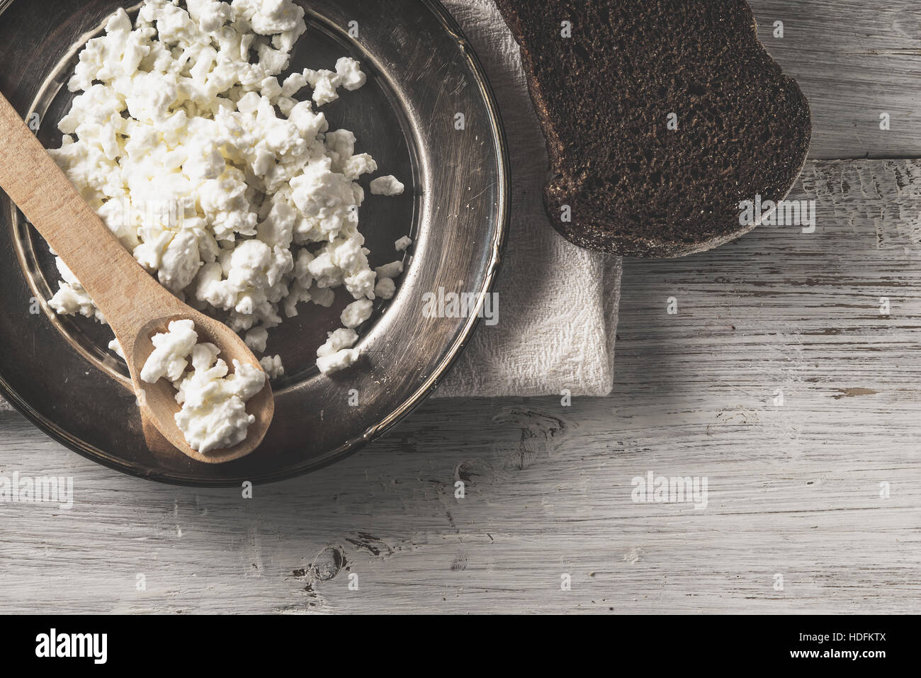 Fresh cottage cheese on the  metal plate  with bread on the white wooden table - Stock Image