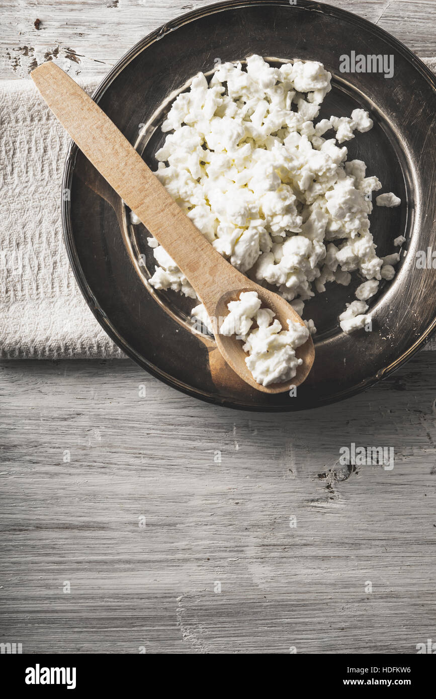 Fresh cottage cheese with wooden spoon on the  metal plate on the white wooden table vertical - Stock Image