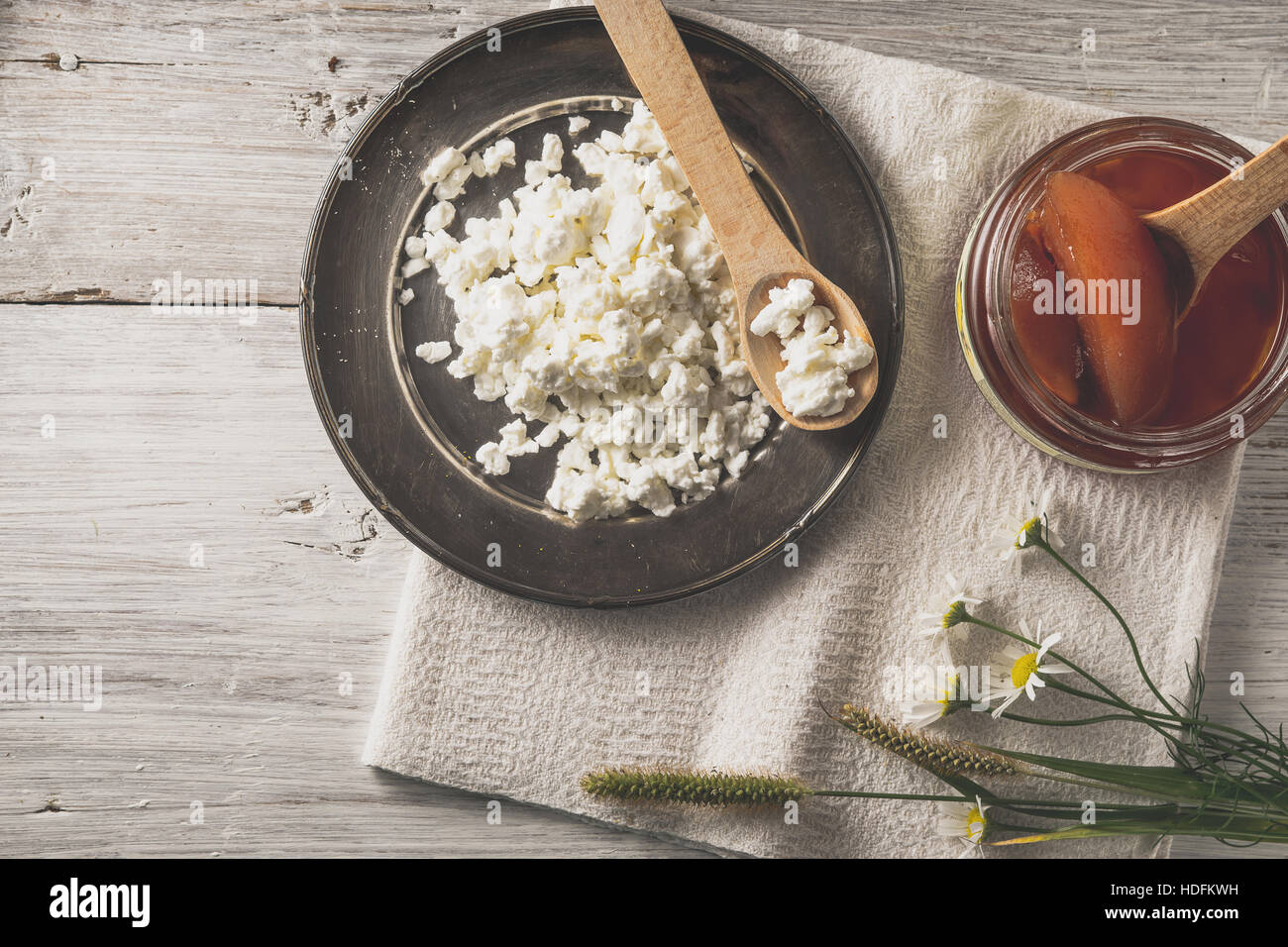 Fresh cottage cheese with  jam and flowers on the white wooden table top view - Stock Image