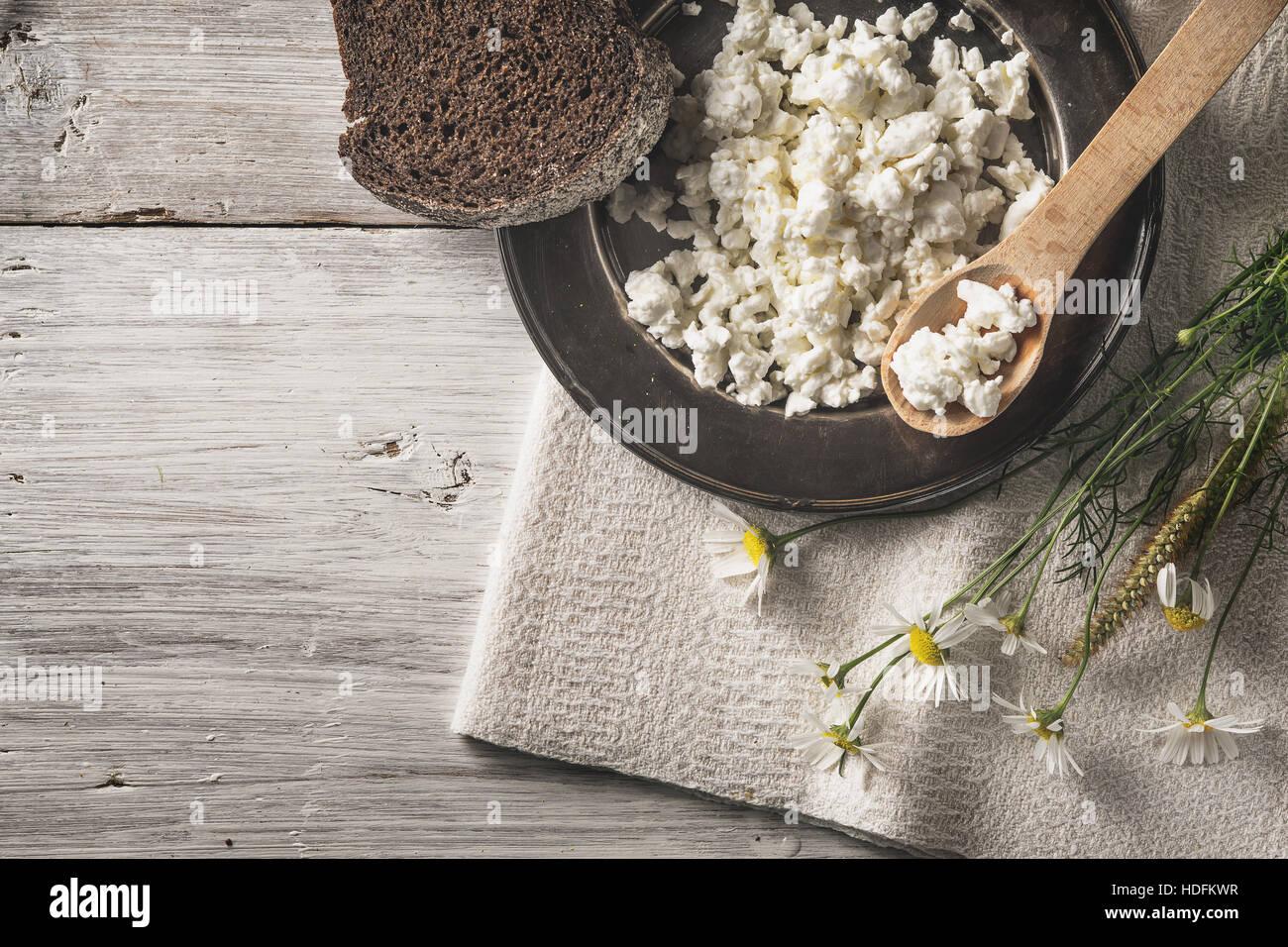 Fresh cottage cheese with bread and flowers on the white wooden table top view - Stock Image