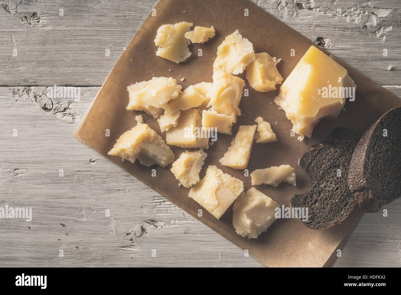 Sliced parmesan with bread on the parchment on the white wooden table top view - Stock Image