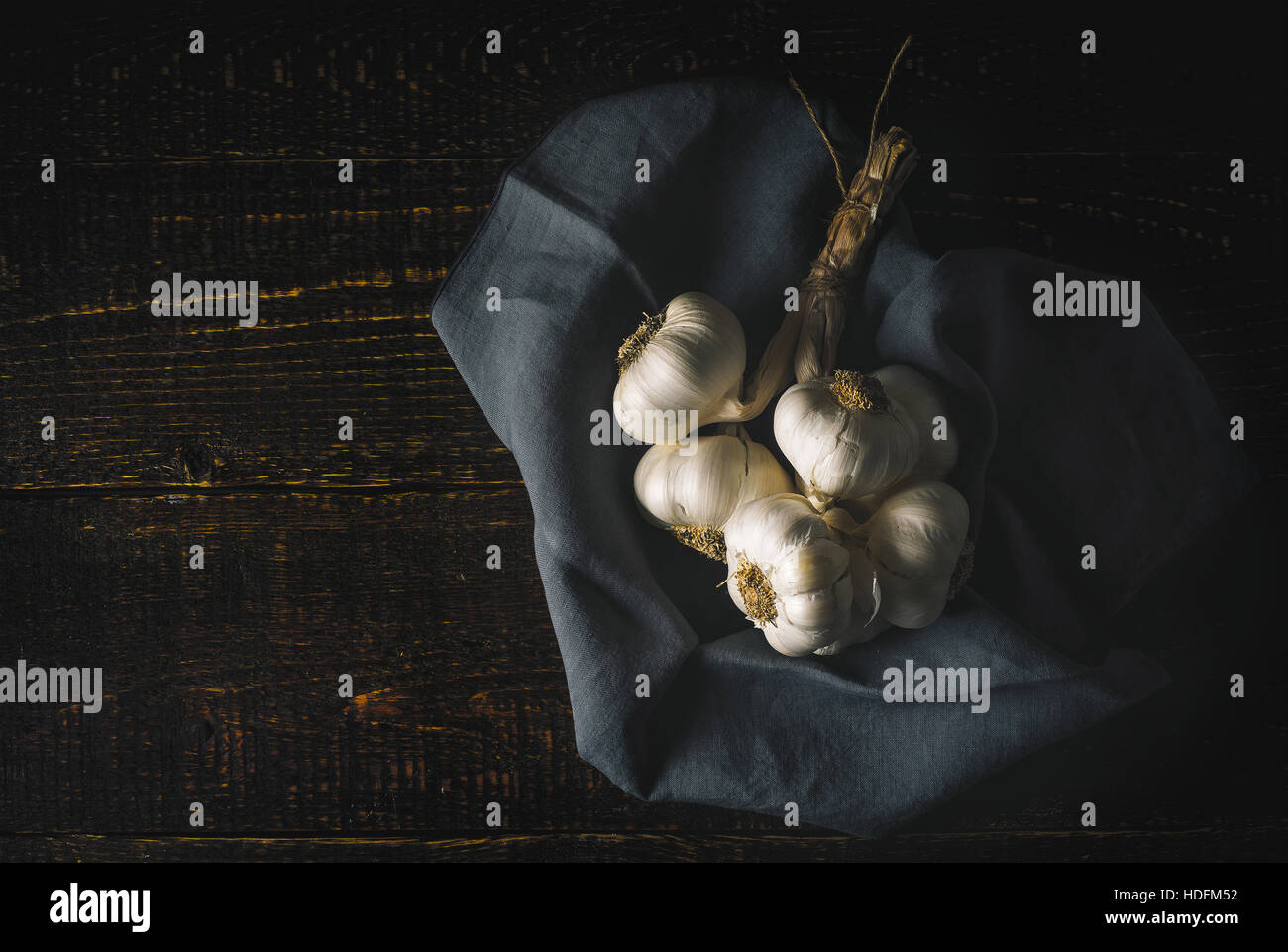 Bunch of garlic with napkin on the wooden table horizontal - Stock Image