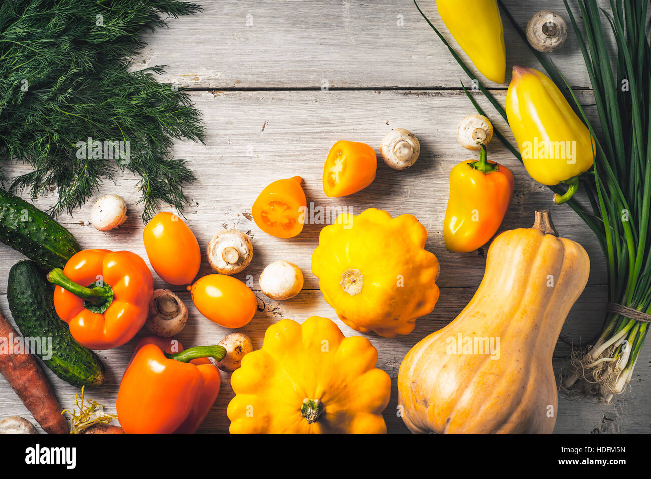 Yellow and green vegetables on the white wooden table top view - Stock Image
