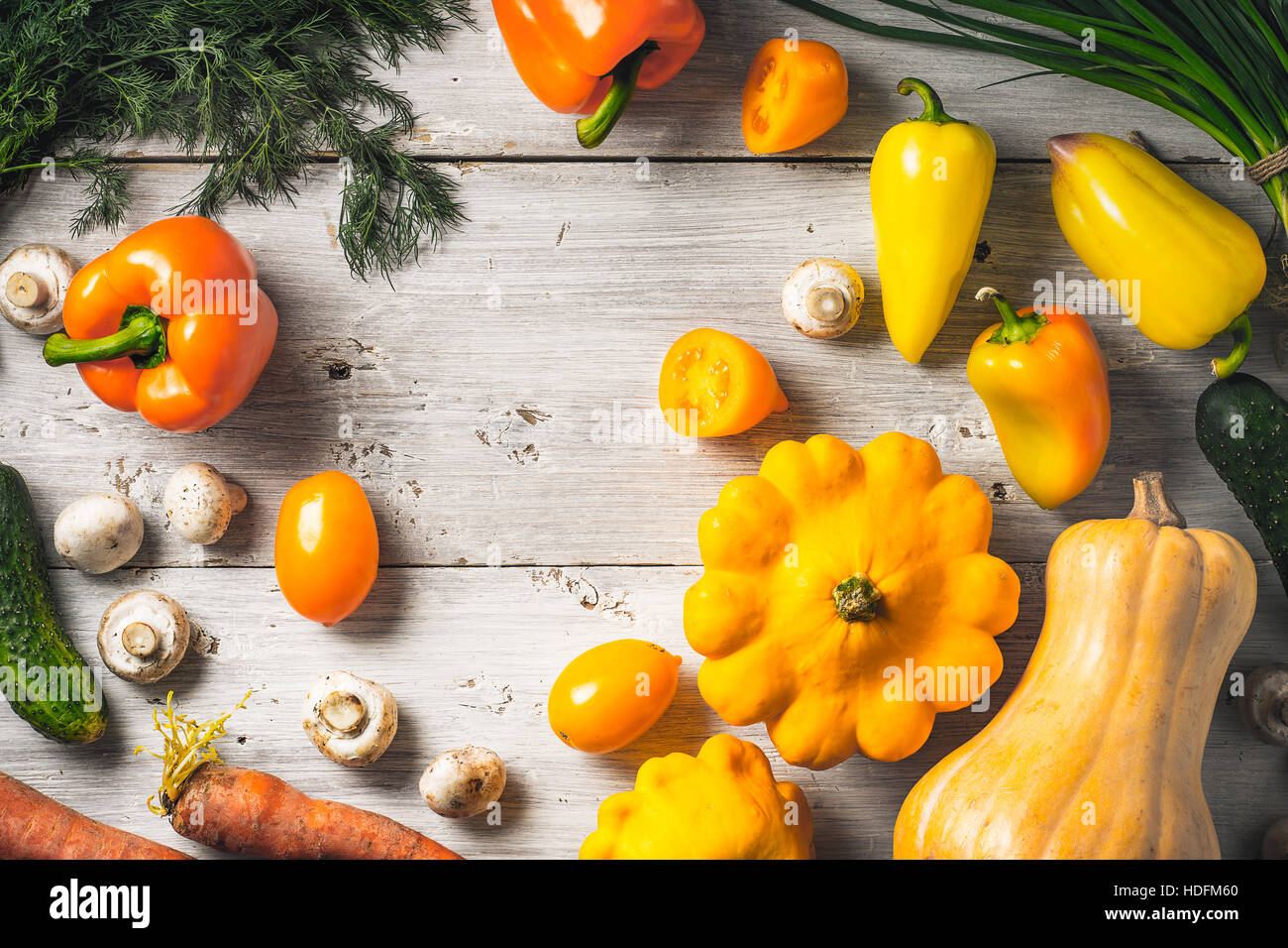 Yellow and green vegetables on the white wooden table - Stock Image