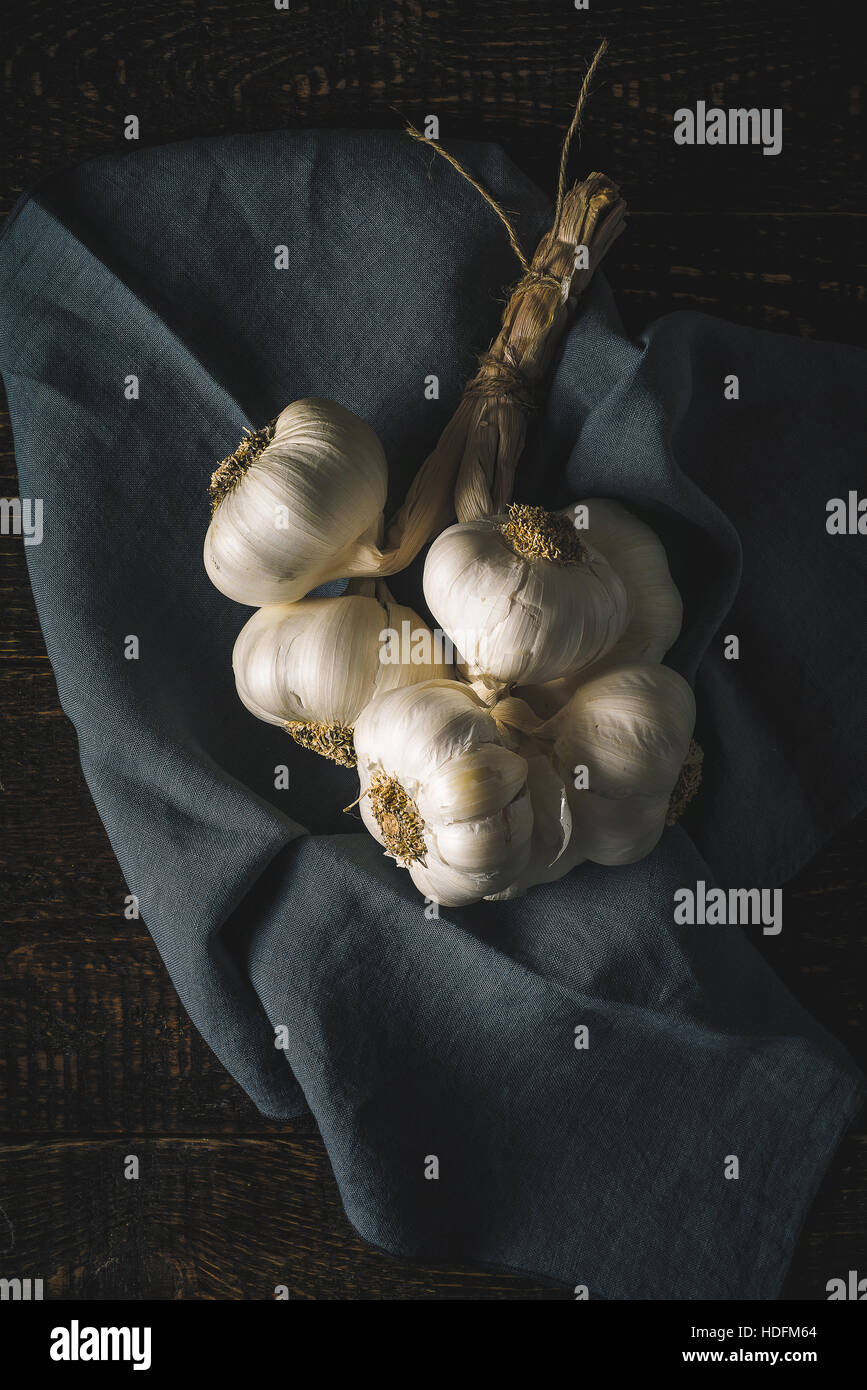 Bunch of garlic with napkin on the wooden table vertical - Stock Image
